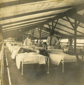 a black and white photograph of a doctor and nurse standing in a tent hospital full of beds.