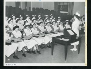 A black and white image of a group of women in nurse uniforms seated in a lecture hall. Another woman in a nursing uniform stands in front of them next to a lectern them.
