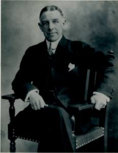 A black and white photograph of Edward Bok, seated with his legs crossed.