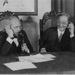 a black and white photograph of two men on a telephone call. One holds a candlestick-style reciever. Both hold speakers up to their ears.