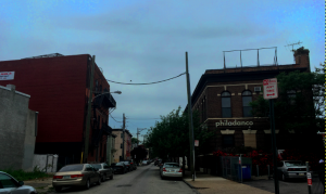 "a color photograph of two brick buildings across the street from one another. The building on the right side of the street has signage reading ""philadanco""."