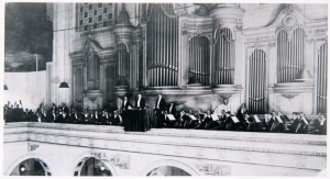 A black and white photograph of the Philadelphia Orchestra led by Leopold Stokowski. The orchestra is on a balcony seated in front of a large pipe organ at Wanamaker's Department Store.