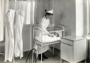 A black and photograph of a nurse in uniform standing over an infant's crib in a hospital room