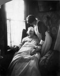 a black and white photograph of a uniformed nurse standing over a seated elderly woman in the elderly woman's home.