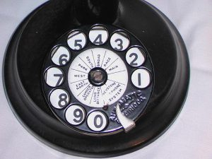 a color photograph of a black rotary telephone dial with white lables