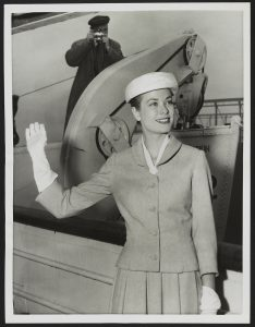 a black and white photograph of Grace Kelly waving. Behind her, a photographer takes a photograph.