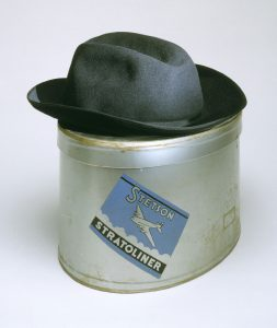 a color photograph of a grey fedora-style hat on a metal hat box with a lable. Text on lable: Stetson Stratoliner