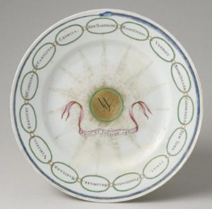 a color photograph of a dinner plate with Martha Washington's monogram and a snake painted on it.