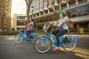 a color photograph of a man and a woman riding blue rental bicycles in Philadelphia.