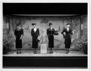 a black and white photograph of four mannequins  dressed in black dresses in a display window of a department store.