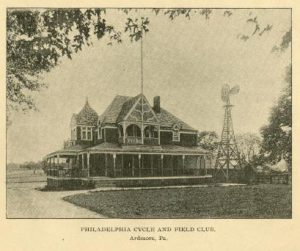 a black and white illustration of the Ardmore Field and Cycle Club, a large victorian-style house with a prominent front porch and windmill.