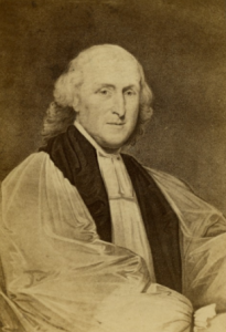 Portrait of Bishop William White. The image is from his waist up. He is seated, with his right arm crossing his body in the lower half of the fram. He is an older white man, bald on top of his head but with longer, curly white hair around the sides and back of his head. He wears a religous robe.
