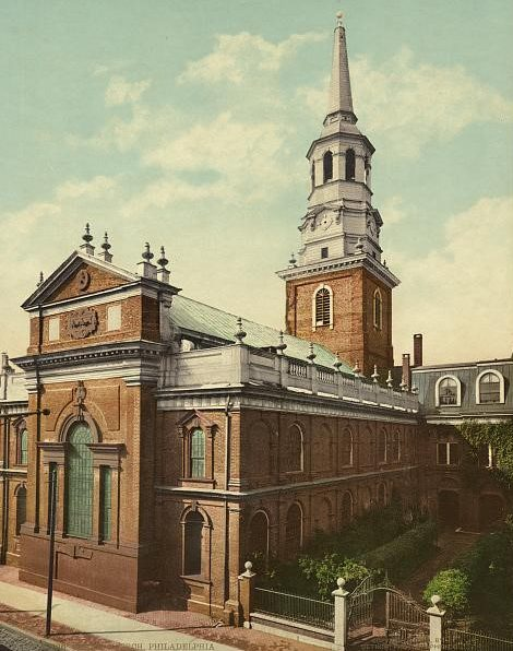 A colorized photograph of Christ Church taken in 1901. A prominent georgian church dominates the photograph, with a gated green courtyard to the right of the main church building.