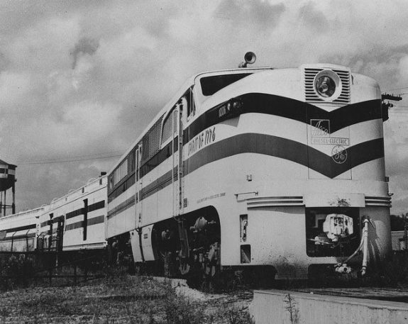 A black and white photograph depicting a 1940s train painted mostly white with a red, white, and blue tribar running horizontally along the center of the train.
