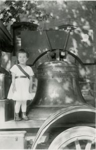 "Small girl wearing white dress and ""Votes for Women"" sash stands next to replica of the Liberty Bell. She and the bell are the same height."