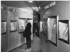 A black and white photograph depicting the zig-zagged interior of the Freedom Train's exhibit car. The walls creating the zig-zag are lined with cases holding historic artifacts.