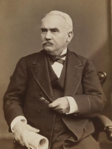 Photogrpah of Morton McMichael. The image is sepia toned. McMichael is an older white man wearing a three piece suit, seated and looking slightly to his right. He holds a rolled up paper in one hand and his pipe in the other, which is across his chest.