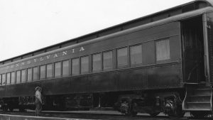 A black and white photograph with a passenger railroad car with word Pennsylvania spelled out above the windows of the train car.