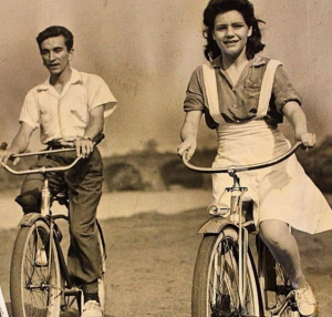 a black and white photograph of a young man and woman riding bicycles in Fairmount Park