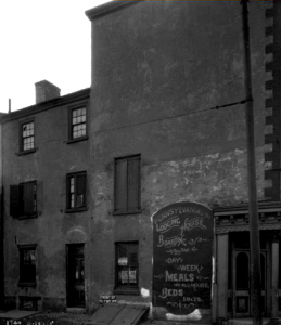 "a black and white photograph of a building with an advertisement for boarding accomodations painted on the front. Text reads ""Pennsylvania Lodging House, Boarding by the Day or Week, Meals served at all hours, Beds 10 & 15"""