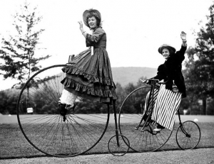 "a black and white photograph of two women in nineteenth century costumes riding ""ordinary"" bicycles."