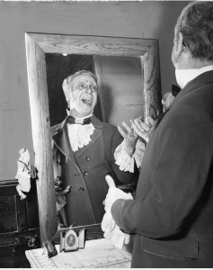 a black and white photograph of a costumed male opera singer practicing in the mirror. The photograph is taken from behind the actor so only his reflection is visible.