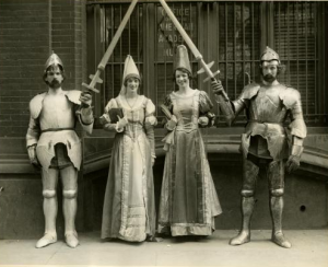 a black and white photograph of four costumed opera perfomers, two male and two female. The males are dressed in suits of armor and hold swords. They stand on either side of the women who are also in medieval dress.