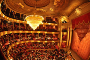 A color photograph of the interior of the Academy of Music showing stage, proscenium, and audience seated under a large chandelier.