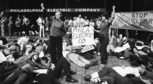 "a black and white photograph of a group of protesters in front of the PECO building. Most of the protesters lay on the ground as if dead. Two in the front hold a sign reading ""Phila. Electric Co."" with their fists raised in the air. Behind them, a large banner reads ""Stop nuclear power"""