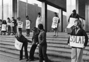 "a black and white photograph of a group of protesters standing on stone steps. Signs read ""Solar"" and ""No Nukes"""