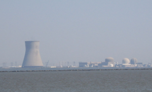 a color image of an artificial island with two nuclear power plants. To the left, a large cooling tower stands. In the foreground the Delaware Bay is visible.