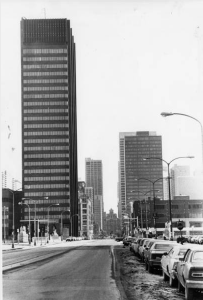 A black and white photograph of the PECO building, a modernist high rise with black cladding and a prominent electronic billboard atop it.