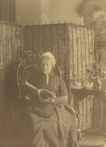 A black and white photograph of Eliza Sproat Turner as an elderly woman. She is seated in a chair reading a magazine.