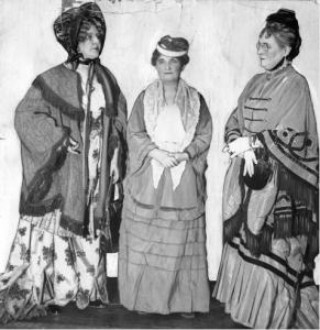 a black and white photograph of three women dressed in costumes reflecting the fashions of 1877.