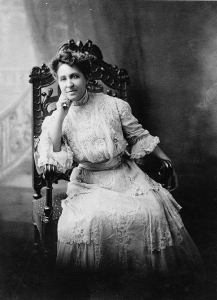 A black and white photograph of Mary Church Terrell seated in an ornately carved chair