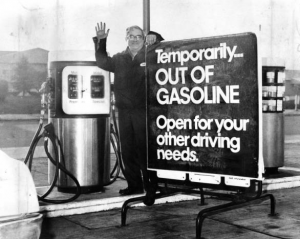"a black and white photograph of a gas station attendant standing next to a gas pump and a sign. Text on sign: ""Temporarily out of gasoline. Open for your other driving needs"""