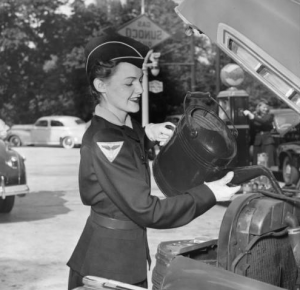 a black and white photograph of a woman pouring radiator fluid into a car. She is wearing a work uniform, white gloves, and a hat.