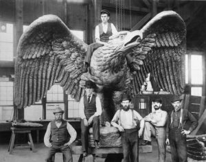 Employees from Tacony Iron Works pose next to a bronze eagle statue they made for City Hall