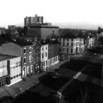A black and white photograph of a collection of historic rowhomes on Cooper Street in Camden, New Jersey.