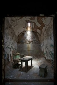 a color photograph of a prison cell with paint and plaster falling off of the wall and collects on the ground. There is a badly decayed chair, table, and stool. Above, light shines through a narrow slit-shaped sky light.