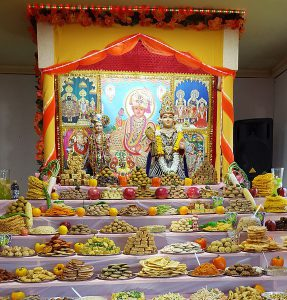 A color photograph of a hindu shrine with many plates of food set out in front of it.
