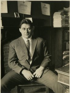 Black and white photograph of Michael Dorizas sitting, wide legged, behind his desk at the university of pennsylvania. He is middle aged with dark hair and wears a full suit with tie.