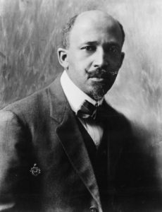 A black and white photograph of W.E.B. DuBois at around ate 50. He wears a dark suit and bow tie.