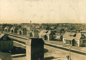 Sepia-toned photograph of a village of one-and-a-half story bungalows.