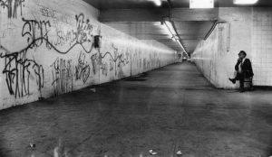 A guard surveys an empty corridor in a subway concourse