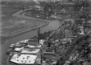 Black and white aerial photograph showing large industrial complex owned by the Heinz corporation along the right bank of the Salem River as well as homes and other buildings.