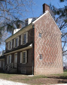 Color photograph of two story, three bay, brick home taken from the front right corner of the building in order to showcase the pattern brick-work on the side of the home.