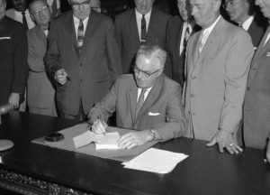A black and white photograph of Mayor Tate signing the new zoning code for Philadelphia.