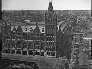 A black and white photograph of Broad Street Station, a gothic revival building with a church-like steeple. Attached to the rear is a large train shed and a viaduct that stretches into the distance. Residential and commercial development runs along either side of the viaduct.