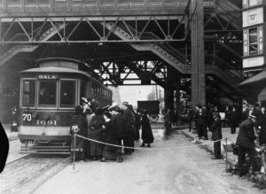 A black and white photograph of a group of people waiting to board a street car. The street car is stopped under the elevated tracks of the Market Frankford Line